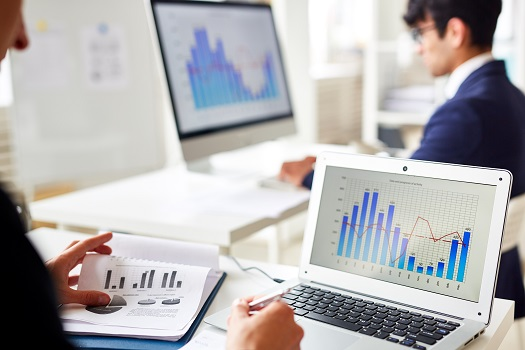 Statistics chart on laptop display and trader analyzing the data